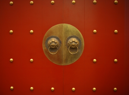 Typical old Chinese red door with bronze dragon knocker photo