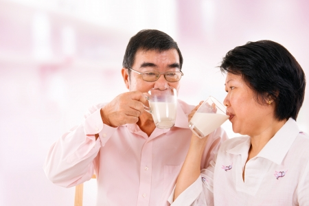 Southeast Asian mature couple drinking soy milk at home.  Stock Photo