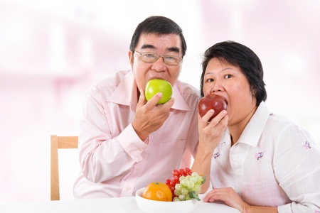 Southeast Asian mature couple eating fruits at home.
