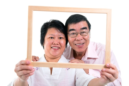 Smiling old Southeast Asian couple looking through an empty frame, isolated on white background Foto de archivo