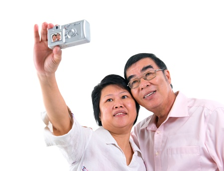 compact camera: Southeast Asian senior couple self photographing, isolated on white