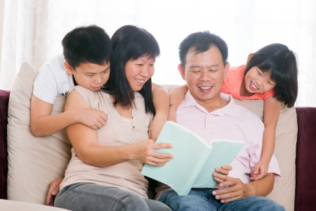 father teaching daughter: Southeast Asian family living lifestyle. Parents and children reading books at home.