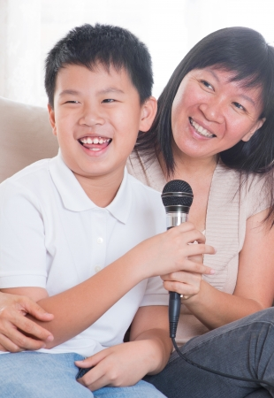 Southeast Asian family living lifestyle. Portrait of a happy Asian family singing karaoke through microphone in the living room photo