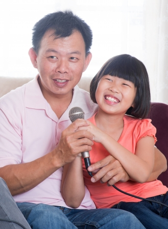 Happy Southeast Asian family living lifestyle. Portrait of a Asian father and daughter singing karaoke through microphone in the living room photo