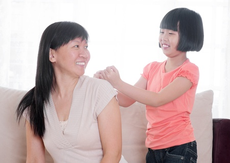 piety: Filial piety concept. Southeast Asian child doing shoulder massage to her mother at home. Stock Photo