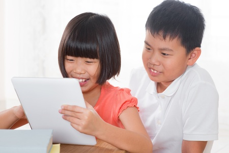 Southeast Asian family living lifestyle at home. Children using digital tablet computer together. photo