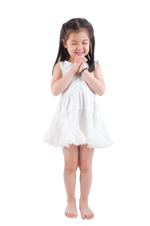 Full body Oost-Aziatische meisje het maken van een wens met glimlachen, staand geïsoleerd op witte achtergrond
