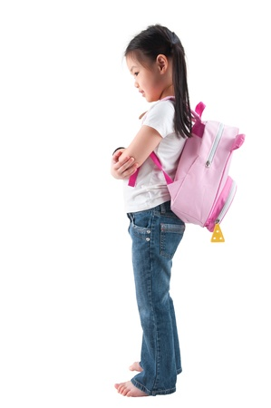 Full body side profile view Asian child elementary student with school bag standing isolated on white background. photo