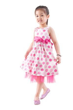 Full body Asian girl in pink dress dancing happily on white background photo