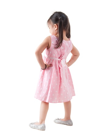 Full body rear view Asian girl in pink dress standing on white background photo