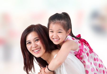 motherhood: Asian family at home. Mother and child piggyback ride at indoor room.