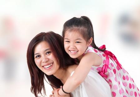 asian home: Famiglia asiatica a casa. Madre e figlio in giro sulle spalle sala interna.