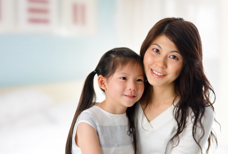 Portrait of adorable young girl and mother at home. Happy Asian family. photo