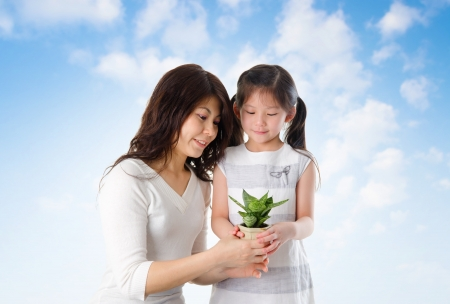 Happy Asian young mother with daughter taking care plant in summer day, blue sky as background. photo