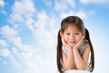 hand chin: Young Asian girl with smile on her face sitting outdoor in summer day, blue sky background