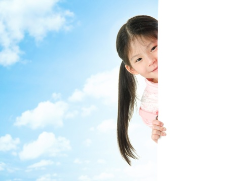 Young Asian girl hiding behind a blank white card in summer day, blue sky as background. photo