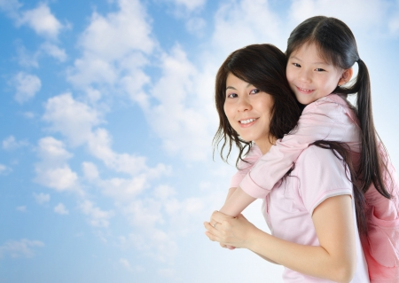 Asian family outdoor fun. Asian mother piggyback her daughter at a nice summer outdoor photo