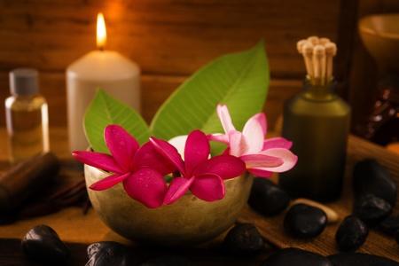 プルメリアの花、エッセンシャル オイル、禅石とテーブル、禅概念上アロマキャンドル スパ設定。