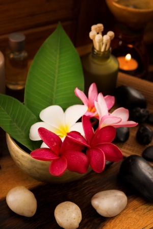 rejuvenate: Spa still life setting with aromatic candles, frangipani flower, cold and hot stones. Stock Photo