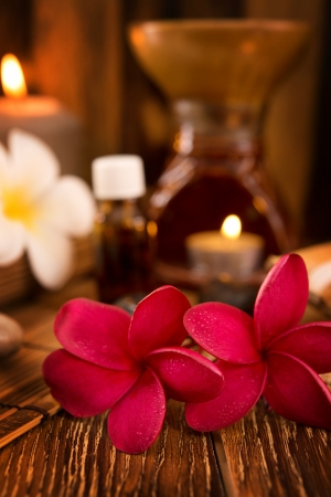 Spa treatment setting with frangipani ,pure essential oil and burning candle.