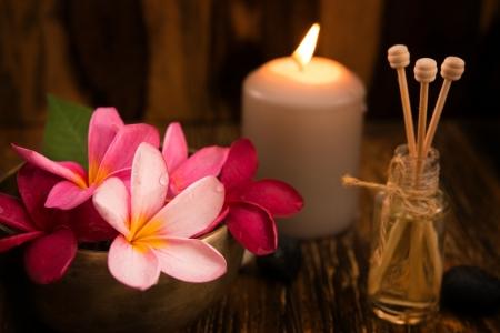 Balneario y concepto de spa con velas, flores frangipani, sándalo y palos de mimbre sobre la mesa de masajes. Foto de archivo