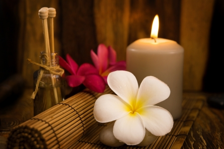 Low light spa setting indoor with candle, frangipani and aroma set. photo