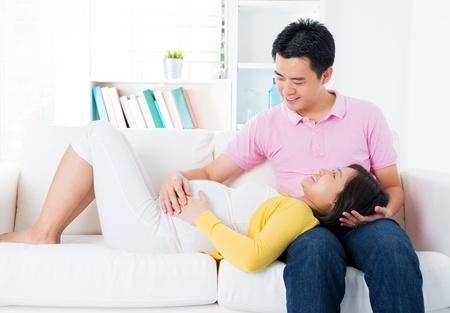 Asian pregnant couple having conversation at home. Asian family living lifestyle. photo