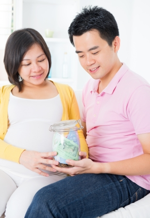 Asian family financial planning concept. Young pregnant couple saving money for future. Living lifestyle at home. photo