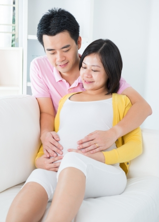 Pregnant woman with husband sitting on sofa, holding hands on belly photo