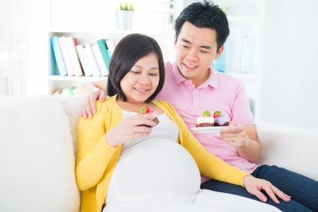 Young Asian pregnant woman and husband eating sweet cake at home Stock Photo - 18494889