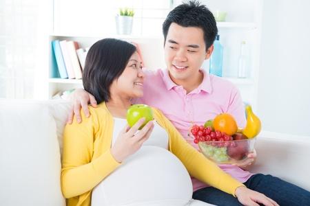 pareja comiendo: Mujer embarazada que come las frutas en casa. Embarazo concepto par de atenci�n m�dica.