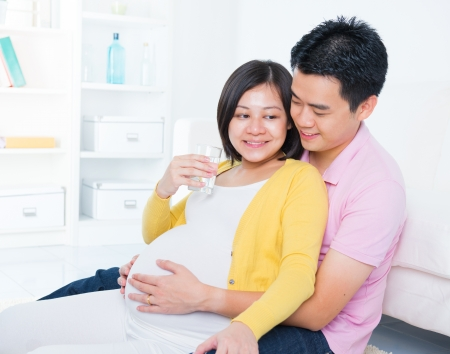 Pregnant woman drinks glass of water at home. Pregnancy couple healthcare concept. photo