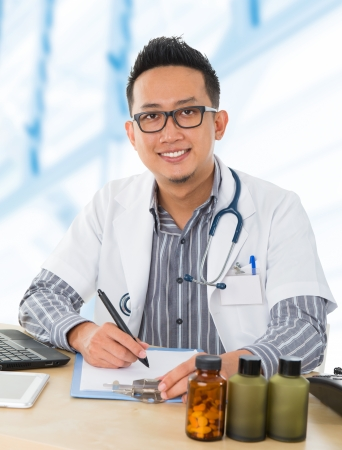 Young Southeast Asian medical doctor working on his desk, inside hospital room. photo