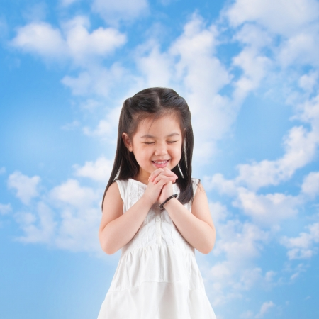 grace: East Asian girl making a wish with smiling, blue sky as background Stock Photo