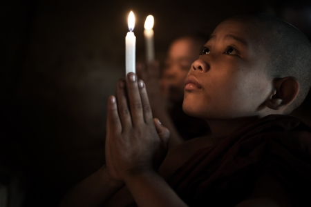 Little monks praying with candlelight photo