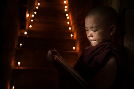 Little monk reading book inside monastery photo