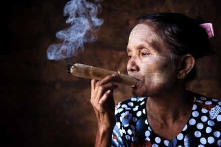 Old wrinkled Asian woman smoking traditional tobacco. Bagan, Myanmar. photo