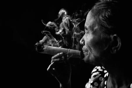 birma: Oude gerimpelde Aziatische vrouw roken traditionele tabak in monotone, zwart-wit portret. Bagan, Myanmar. Stockfoto