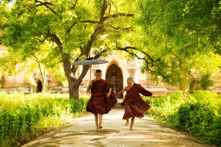 Two little monks running outdoors Stock Photo
