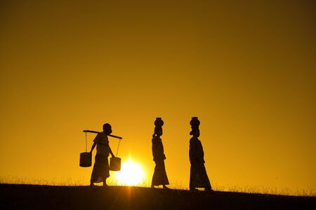 Silhouette of Asian traditional farmers carrying clay pots on head going back home, Bagan, Myanmar photo