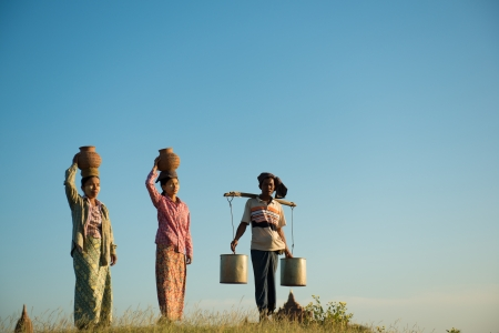 paddy field: Group of Asian traditional farmers carrying clay pots on head going back home, Bagan, Myanmar Stock Photo