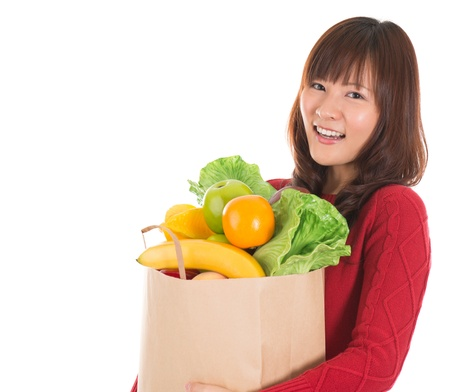 grocery stores: Happy smiling young Asian woman holding paper shopping bag full of groceries isolated on white