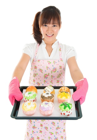 Young Asian female baking bread and cupcakes, wearing apron and gloves holding tray isolated on white. photo