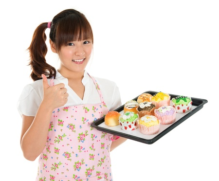 Thumb up Young Asian female baking bread and cupcakes, wearing apron and gloves holding tray isolated on white. photo