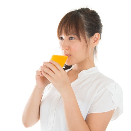 Young Asian woman drinking orange juice, isolated on white. photo