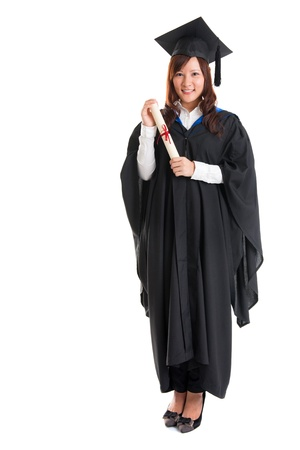 Full body happy Asian female student in graduation gown standing isolated on white background