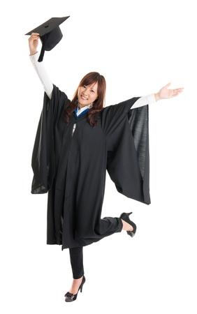 全身興奮的亞洲女學生在畢業禮服,手舉起張開雙臂,跳躍在白色背景孤立