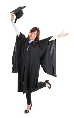 Full body excited Asian female student in graduation gown hands raised open arms jumping isolated on white background photo