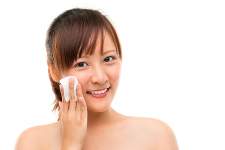 Skin care woman removing face makeup with cotton swab pad, skin care concept. Facial close up of beautiful mixed race Asian. Girl isolated on white background photo