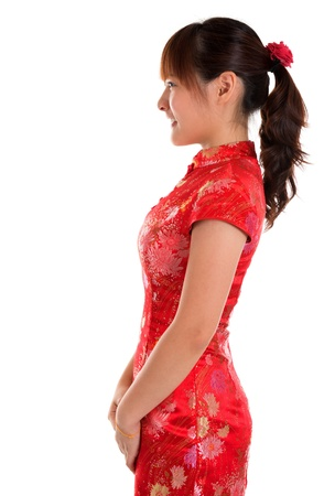 Side view of beautiful oriental woman in red traditional Chinese cheongsam, standing isolated on white background. photo